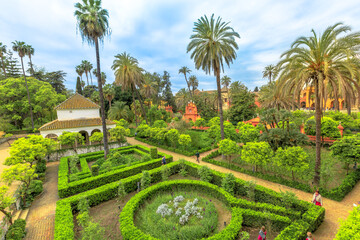 Seville, Andalusia, Spain - April 19, 2016: gardens of Royal Alcazars of Seville, one of great complexes of Spanish courtor, or Reales Alcazares, Andalusian Architecture and old Arab Palace.