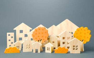 City of figures houses and autumn yellow trees. Real estate concept. Urbanism and infrastructure. Realtor services. Affordable housing. Changing seasons. Travel and tourism in the cities of the world.