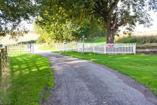 White picket fence alongside a country lane with an open gate.