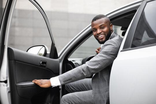 Black man in suit getting in car