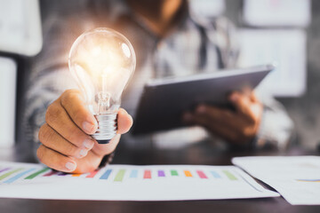 Successful business idea and creative innovation concept, close up business man holding lighting bulb and tablet with financial graph on table