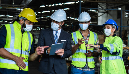 Industrial engineers and businessman in suite and safety helmet wearing mask working in factory,...