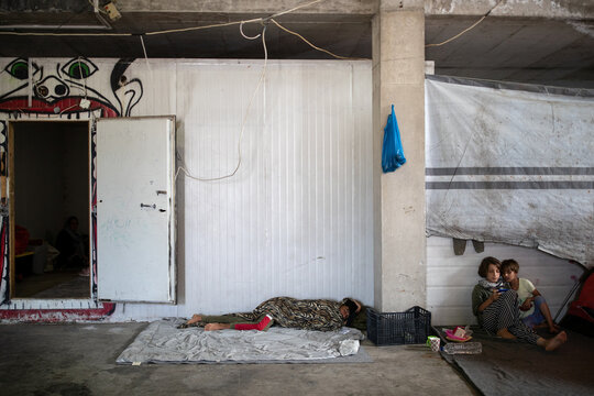 A boy sleeps as refugees and migrants from the destroyed Moria camp find shelter in a warehouse near a new temporary camp, on the island of Lesbos