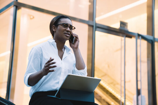Stressful black executive woman talking on mobile phone