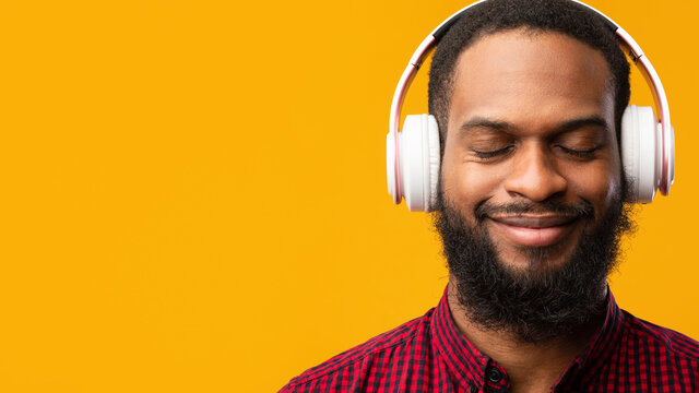 Smiling black man enjoying music using headphones