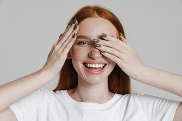 Image of happy ginger girl smiling and covering her eyes