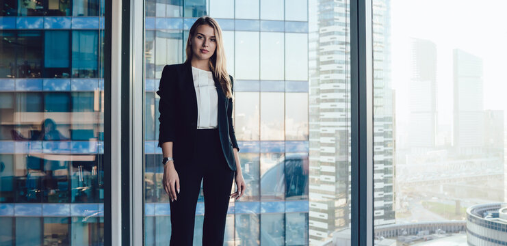 Half length portrait of pretty blonde business woman in trendy elegant formal wear standing near window in office interior, confident beautiful 30s female executive manager in suit looking at camera