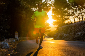 Close-up of young man running down a road with big pine trees around with beautiful golden sunset in the background, man is wearing sport clothes and striking Papier Peint