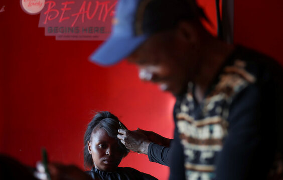 A customer is reflected in a mirror as she is attended by a hair stylist at a saloon in Soweto