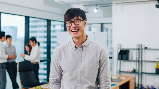 Portrait of successful handsome executive businessman smart casual wear looking at camera and smiling, happy in modern office workplace. Young Asia guy standing relax in contemporary meeting room.