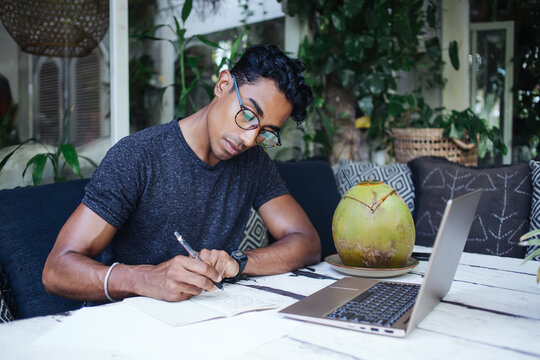 Young concentrated Hispanic male student writing essay at table