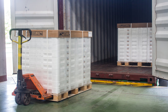 Hand pallet truck loading shipping boxes and goods on wooden pallet at loading dock from container.(Soft focus)