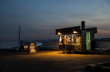 A man buys shawarma at a street food wagon on the embankment of Tom river in Tomsk
