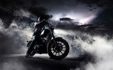 Detail of high power motorcycle chopper with man rider at night.