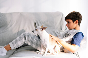 11 year old boy with laptop and dog at home