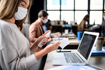 People with face masks disinfecting indoors in office, back to work after coronavirus lockdown.