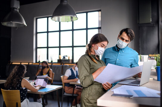 Business people with face masks indoors in office, back to work after coronavirus lockdown.