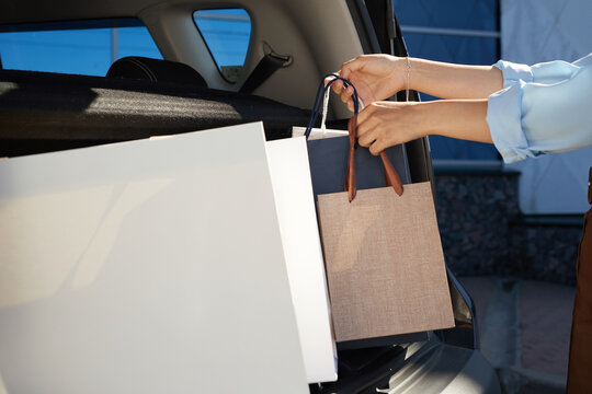 Close up of unrecognizable young woman loading shopping bags in car trunk on parking lot by mall, copy space