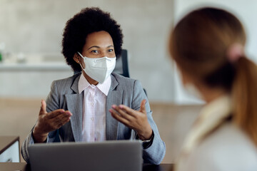 Black female financial consultant talking to her client and wearing protective face mask during the...