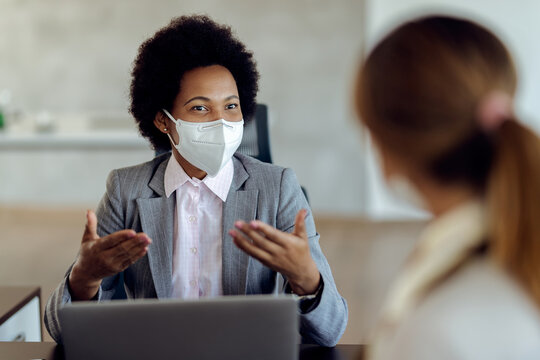 Black female financial consultant talking to her client and wearing protective face mask during the meeting.