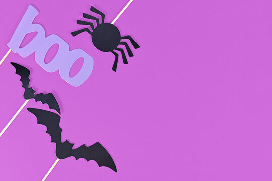 Halloween background with photo porps on sticks in shape of black bats, spider and violet word 'boo' on purple background with copy space