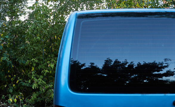 Back window of blue car parked on the street in summer sunny day, rear view. Mock-up for sticker or decals