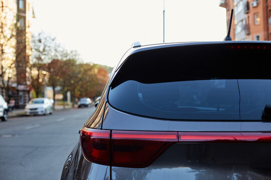 Back window of grey car parked on the street in summer sunny day, rear view. Mock-up for sticker or decals