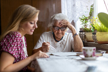 Young woman helping elderly grandmother with paperwork