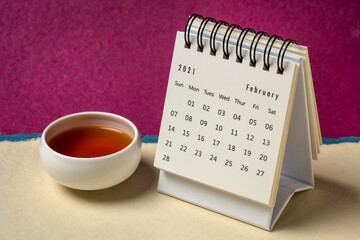 February  2021 - spiral desktop calendar against colorful handmade paper with a cup of tea, season,  time and business concept