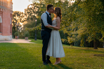 Young Couple Kissing At Green Lawn After Wedding With Sunset on Background.