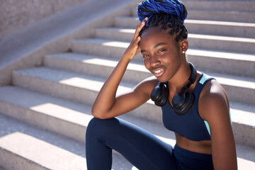 portrait of attractive slim black female having rest after running, take a break, sport workout...