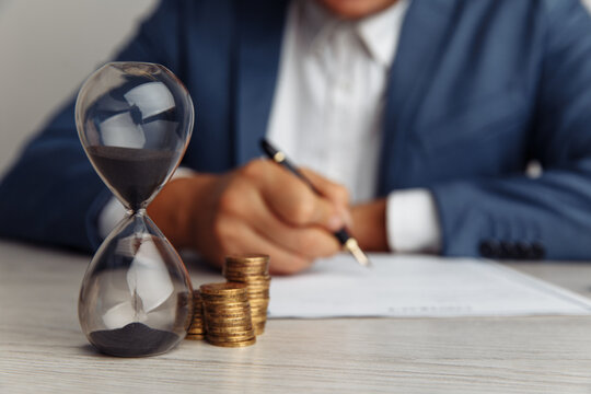 Businessman approves important contract in office. Stack of coins and hourglass on desk close-up. Time is money concept.