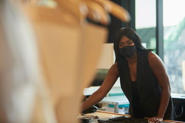 Young black woman working in her design studio wearing a facial mask for coronavirus, pandemic, covid-19 protection.