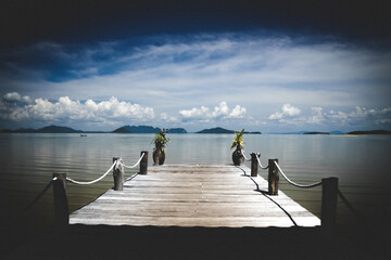 View from tropical island over wood pier on endless ocean water with dramatic storm sky clouds - Thailand, andaman sea