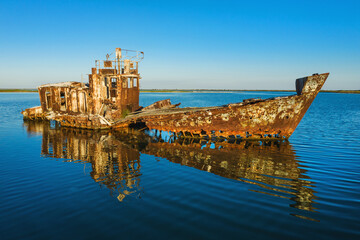 Ruins of old ship wreck on sea shallow with holes in board under sky with copy space