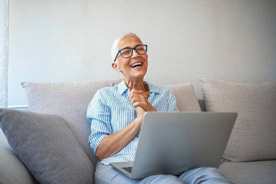 Senior woman making video call on laptop , waving at screen, chatting online with people who distance. Cropped shot of a happy senior woman waving hello while on a video call on her couch at home