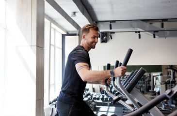 side view portrait of caucasian man workout on a fitness machine at gym, run, healthy lifestyle, sport concept