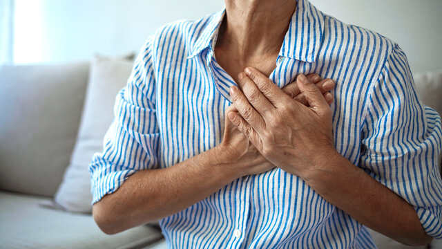 Middle age woman wheezing touching chest at home. Elderly woman having chest pains or heart attack at home. Woman with heart attack holding and massaging her chest