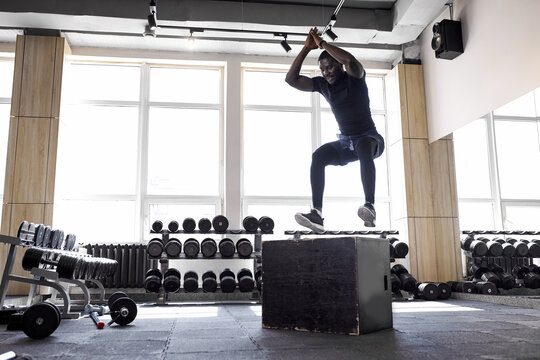 african aportsman perform squats on box in gym, fit guy jump on box, have strong body. sport, fitness, workout, crossfit concept