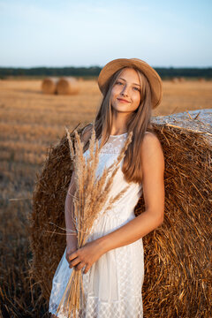 Young blond girl leaning on the bale of straw and holding a bouquet of dried flowers catching last warm sun rays of a setting sun
