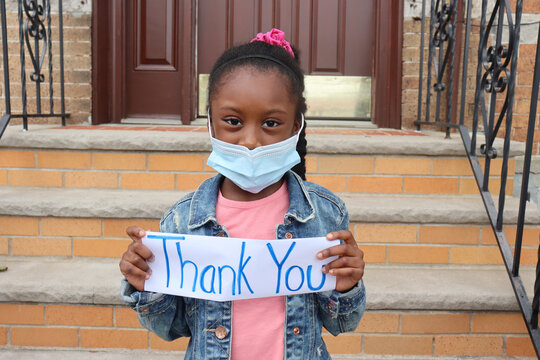 Girl holding thank you sign outside house front steps and door background