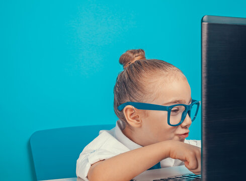 Beautiful cute little girl as businesswoman with eyeglasses and tie smiling while using laptop computer. Closeup of little girl working on her computer at office.