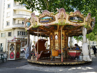 Elegant antique carousel with small horses and other animals running in a French square for the delight of children