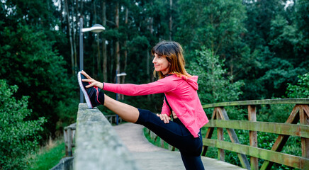 Smiling athlete woman doing leg stretch outdoors