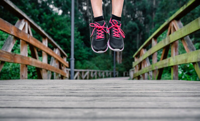 Athlete woman feet with sneakers jumping outdoors