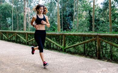 Athlete woman running through a park