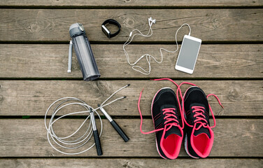 Still life of sports equipment with sneakers and skipping rope