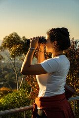 Brunette woman using binoculars on lookout during sunset