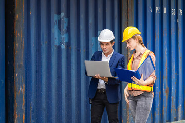 two engineer worker hold a laptop, document for checking a quality of containers box from cargo ship for export and import, blue container background