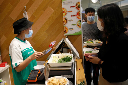 The cashier holds plant-based meatballs produced by Zhenmeat, as customers pay for their meal during lunch time at a Hope Tree restaurant  in Beijing